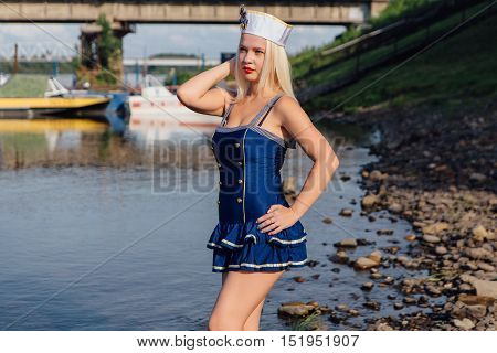 Young retro pinup girl wearing sailor uniform on the river shore