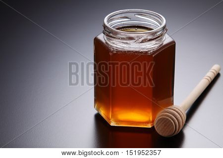 honey in a glass container with wooden dipper