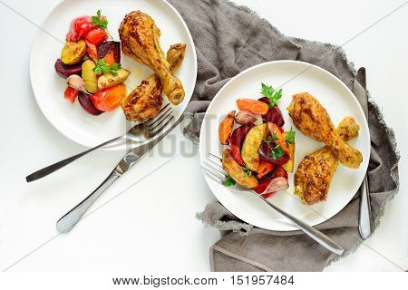 Chicken drumsticks with roasted vegetables garnish in two plates view from above