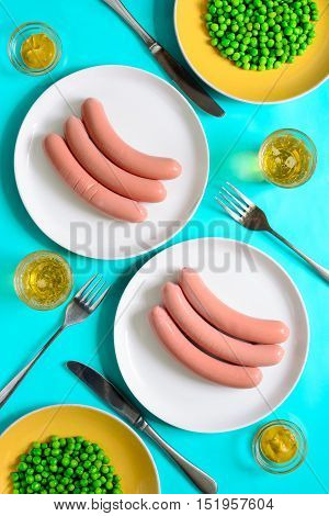 Sausages and beer served with mustard and green peas view from above table setting