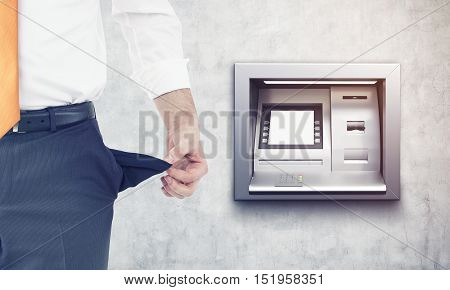 Businessman with empty pockets standing near cash machine in concrete wall. Concept of being broke