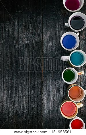 Side frame of colorful liquids in various cups and mugs. Flat lay