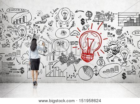 Rear view of businesswoman drawing at concrete wall with giant red light bulb sketch and startup icons.