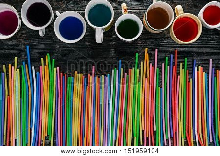 Colorful liquids in cups and mugs with drinking straws. Flat lay