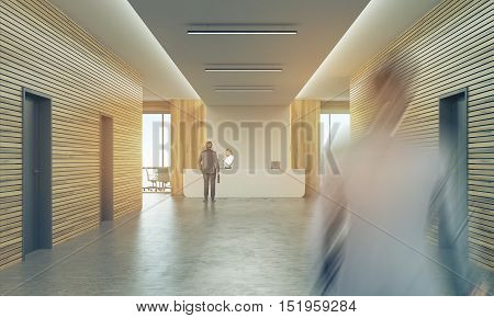 People In Sunlit Office Corridor With Reception Counter