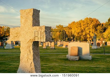 Cross in a cemetery with large maple trees in the background in autumn (Beloeil Quebec Canada)