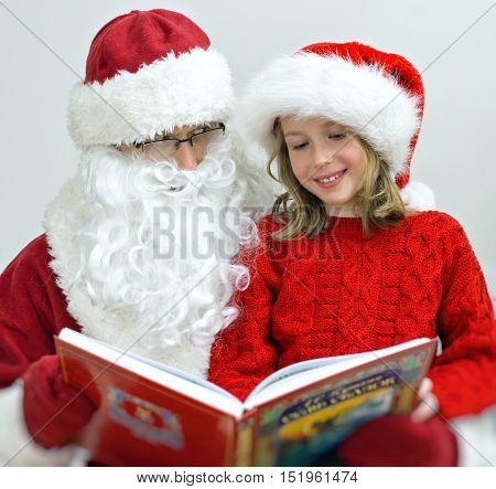 Santa Claus And Little Girl Reading Fairy Tales At Christmas.
