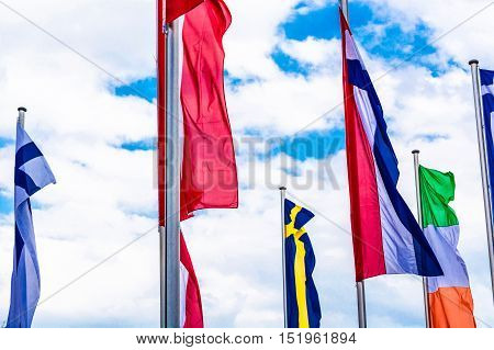 Several Europe countries flags arranged in front of a blue sky.