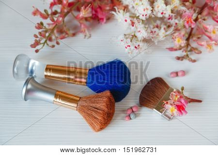 There White and Pink Branches of Chestnut Tree.Two Make Up Brown and One Blue Brushes are on White Table.Selective Focus