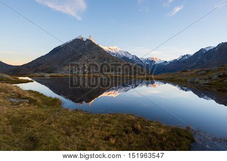 High Altitude Alpine Lake In Idyllic Land With Reflection Of Majestic Rocky Mountain Peaks Glowing A