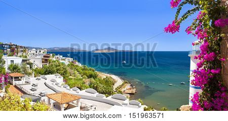 Beautiful flowers can be seen past the Lighthouse at Ortakent in Turkey with blue/green seas stretching to the horizon