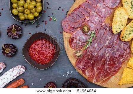 Plate with spanish jamon ham and chorizo tapas, picnic table top view