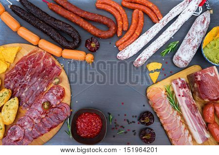 spanish tapas with salami, chorizo, lomo, jamon with red hol salsa sause and olives, picnic table, top view frame with copy space