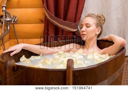 Spa. Girl relaxing in bath with oils and rose petals