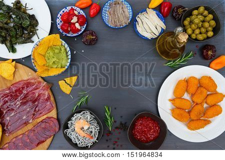 Table with spanish tapas - anchovies, peppers padron, jamon, croquetes, guacamole, hot salsa and olives, frame with copy space