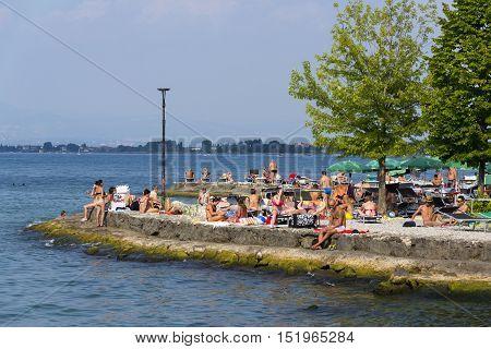 Desenzano Del Garda, Italy - July 30: People Sunbathing On Beach On 30 July 2016 In Desenzano Del Ga