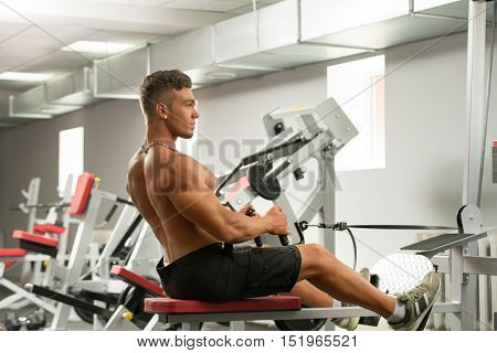 At gym. Photo of sexy young man trains on simulator
