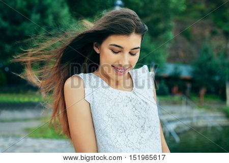 modest young beautiful girl in a white dress with long hair. The concept of lifestyle