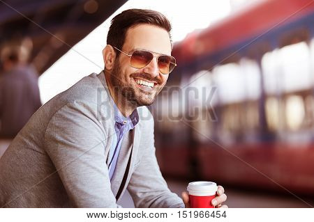 Young businessman on railroad station is waiting for train and drinking coffee.
