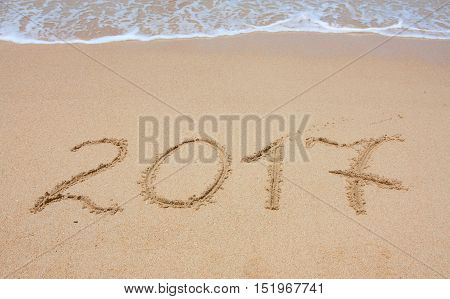 Year 2017 written in sand at the beach