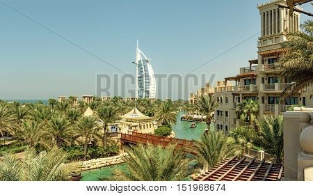 DUBAI, UAE - OCTOBER 14, 2016: A panorama of the iconic Burj al Arab set against green palm trees and the artificial lake in Al Qasr Hotel