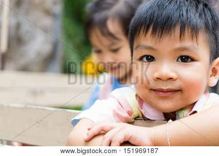 Happy Asian children are riding on a truck. Smiling Asian boy face with her sister on the background. Happy Asian children with copy space.