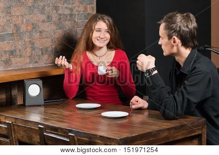 Smiling woman in a red sweater drinking coffee and gesticulating explains something to the man sitting next