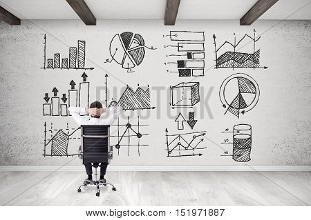 Rear view of businessman sitting in his armchair with arms behind head and looking at diagrams and graphs on concrete wall.