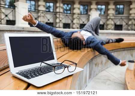 Tired Asian businessman is resting on a bench near his office. His laptop and glasses lie beside him. Concept of work and rest