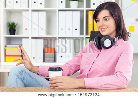 Dreamy girl in pink shirt and blue jeans is sitting with her coffee cup and large headphones in office and daydreaming. Concept of vivid imagination