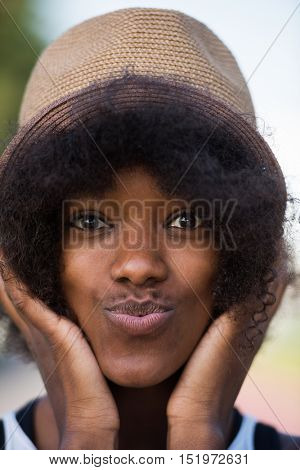 Close up portrait of a beautiful young african american woman smiling and looking up on a beautiful sunny day