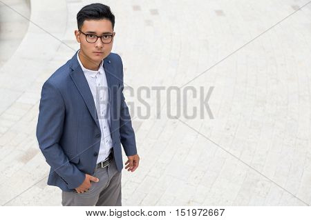 Serious young Asian businessman in dark blue vest and gray pants is looking at the viewer with confidence. Concept of high self esteem. Mock up