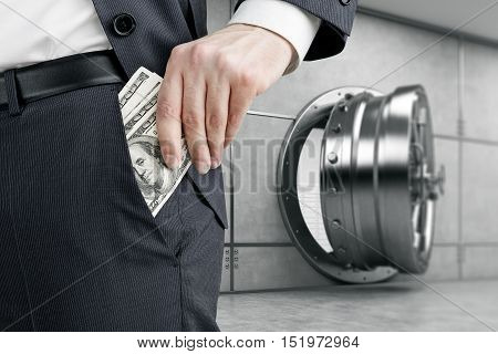 Close up of businessman putting several dollar notes into his pocket while standing against slightly open vault door. 3d rendering.