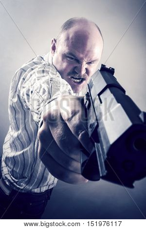 Frustrated mature businessman aiming gun over white background