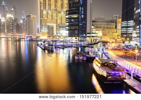 DUBAI UAE - SEPTEMBER 11: The night illumination of Dubai Marina and Dhow boat on September 11 2013 in Dubai UAE. It is an artificial canal city built along a two mile (3 km) stretch of Persian Gulf shoreline.