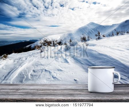 Mug of tea on wooden table against background of winter mountains