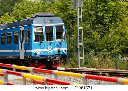 Djursholm, Sweden - July 15, 2016: Suburban train on the Roslagsbanan railroad line 29 with destination Stockholm Ostra pass the level crossing with folded booms at Djursholms