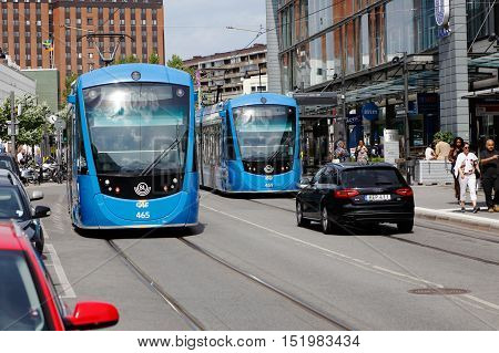 Solna, Sweden - June 15, 2016: Two trams in traffic for the Stockholm public transport at the tram stop on the tramway Tvarbanan meet at Svetsarvagen street in Solna Business Park.