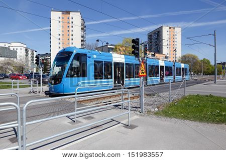 Solna, Sweden - May 6, 2016: Blue tram of class A35 on the Tvarbanan line at the road crossing with Gransgatan.