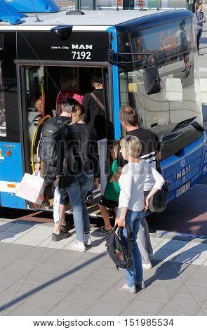 Stockholm, Sweden - June 2, 2016: People boarding a blue city bus on line 2 with final destination Sofia at Slussen bus stop.
