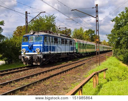 blue locomotive pulling green carriages, summer, sunny day