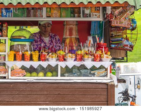 Bogota Colombia - April 30 2016: A woman selling fresh fruits from a stand on the street of Bogota