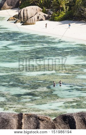Some early tourists on the beach and snorkeling in the lagoon of Anse Source D'Argent in La Digue Seychelles