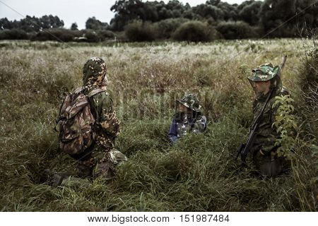 Dramatic hunting scene with group of hunters in rural field in expectation of hunting in tall grass during hunting season