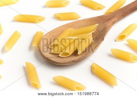 Penne into a spoon isolated on white background