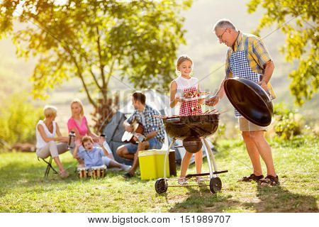 granddaughter making barbecue with grandfather on camping