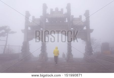 A chinese woman walking towards one of the landmark gates on top of Taishan or mount tai in Shandong province china.