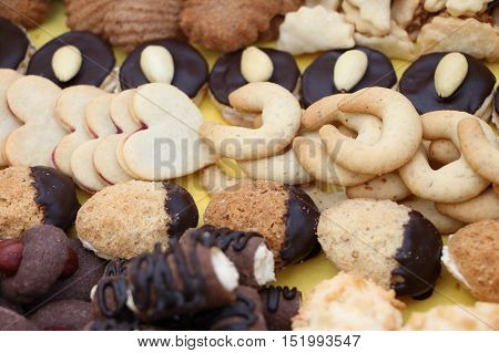 Detail photo of various homemade Christmas cookies special Czech sweets on yellow background. Pastry cookies biscuit cracker with spice (vanilla cinnamon) and nuts (walnuts) similar as tea biscuits