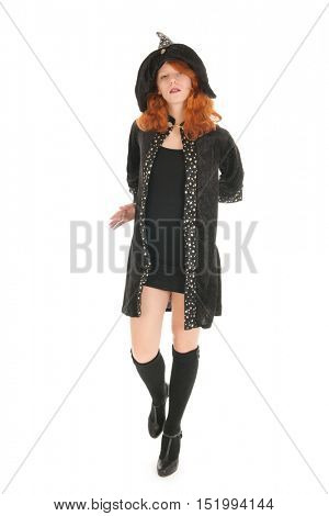 Young woman with red hair as evil witch walking isolated over white background