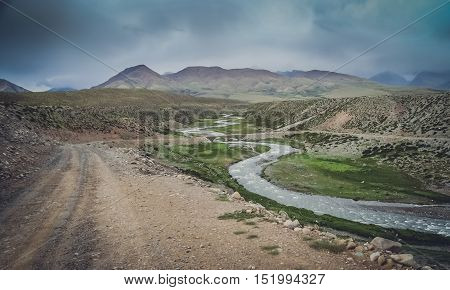 Mountain road through the beautiful valley in Central Tibet, China